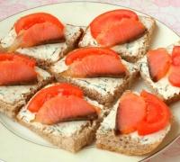 Шаг№4 - Ломтики хлеба смазать плавленным сыром, на каждый положить по кусочку сёмги и дольке помидора.