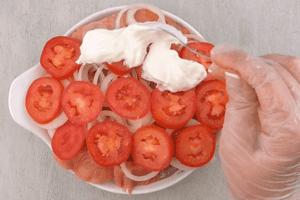 На лук уложить помидоры, смазать слоем сметаны