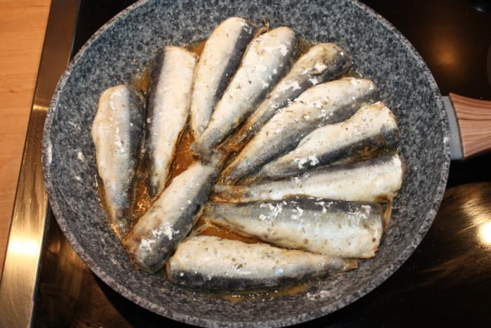 Свежая салака жареная на сковороде в муке