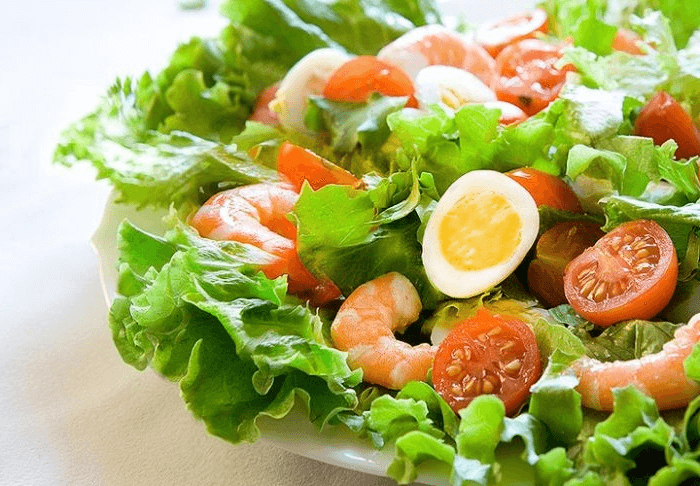 Кладем листья салата, далее морепродукты, яйца и помидоры