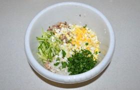 Готовый, промытый холодной водой рис кладем в миску, добавляем размятую вилкой сайру, крупно тертые яйца и огурец, а также замаринованный лук и порубленную зелень, перец и соль.