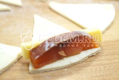 В каждый кусочек теста завернуть ломтик рыбы и брусочек сыра.